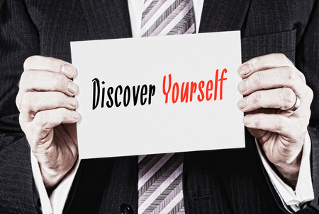 discover: A businessman holding a card with the words, Discover Yourself.