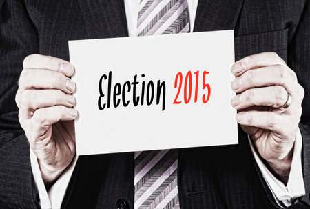 Businessman holding a card with Election 2015 written on it. Stock Photo