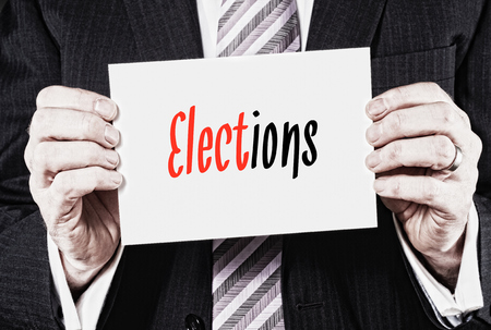 Businessman holding a card with Elections written on it. Stock Photo