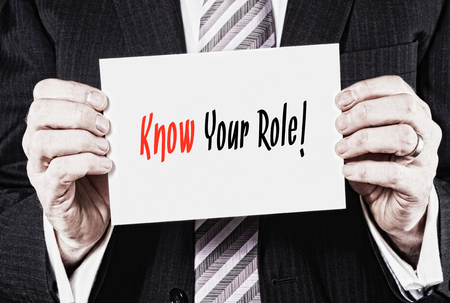 r�le: Un homme d'affaires tenant une carte avec les mots, Know Your Role, �crit � ce sujet.