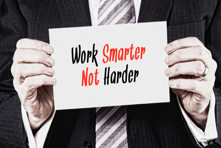 smarter: A businessman holding a business card with the words,  Work Smarter Not Harder. Stock Photo