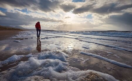 A woman walking the beach at sunset alone with her thoughts. photo