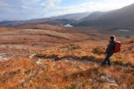 clair: A hiker and their dog descending the summit of Beinn Eighe with Loch Clair in the distance. The Scottish Highlands.