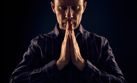 implore: A front view of a man praying in the dark with a ray of sunlight shining down on him