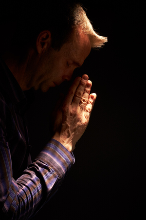 implore: A side view of a man praying with a ray of sunlight shining down on him