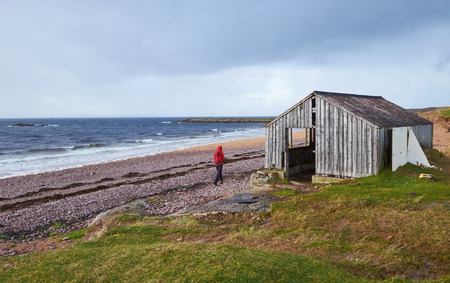 away from it all: A hiker exploring a remote beach in the Scottish Highlands in Autumn.