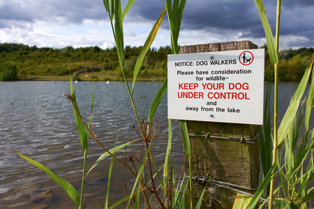 under control: A sign warning owners to Keep their dog under control at a wildlife conservation park. Stock Photo