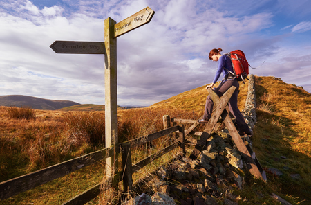 A woman crossing a stile on the Pennine Way, English Countryside walk.UK