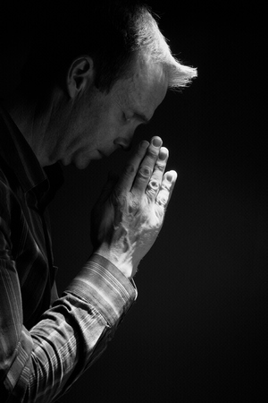 worshipper: A front view of a man praying in the dark with a ray of sunlight shining down on him