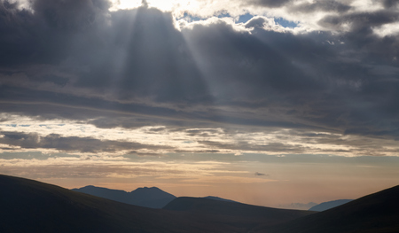 fells: Rays of  sunlight through the clouds over the valley surrounding Braithwaite & Derwent Fells, in the Lake District, Cumbria, England. UK.