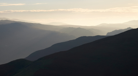fells: Warm morning sunlight over the valley surrounding Braithwaite, Derwent Fells, from the trail leading from Grisedale Pike in the Lake District, Cumbria, England. UK. Stock Photo