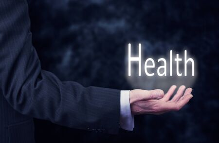care providers: The arm of a businessman holding the word Health.