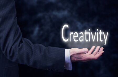 vision business: The arm of a businessman holding the word Creativity.
