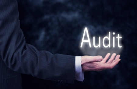 auditors: The arm of a businessman holding the word Audit.