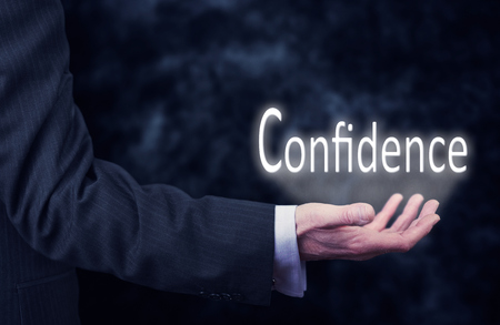 The arm of a businessman holding the word Confidence.