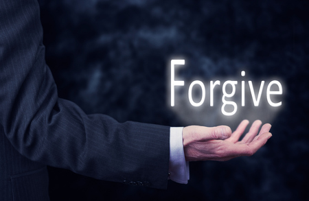 perdonar: El brazo de un hombre de negocios la celebración de la palabra perdonar.