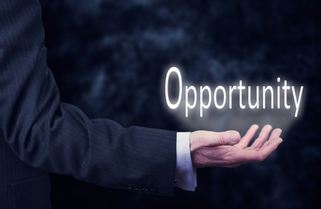 achievable: The arm of a businessman holding the word Opportunity.