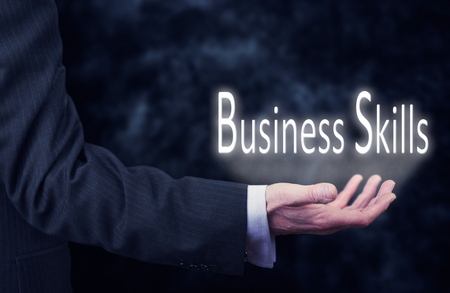 interpersonal: The arm of a businessman holding the words Business Skills. Stock Photo