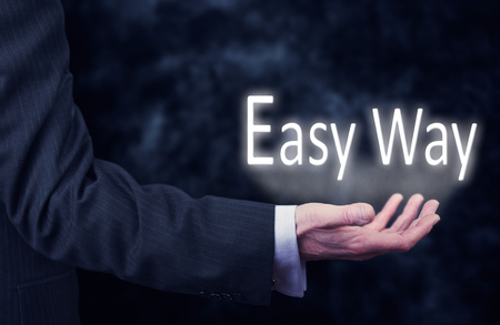 cogent: The arm of a businessman holding the words Easy Way. Stock Photo