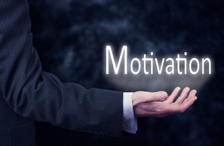 The arm of a businessman holding the word Motivation. photo