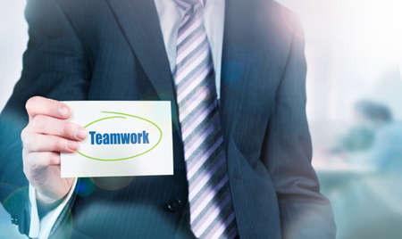 synergism: Businessman holding a card with Teamwork written on it.