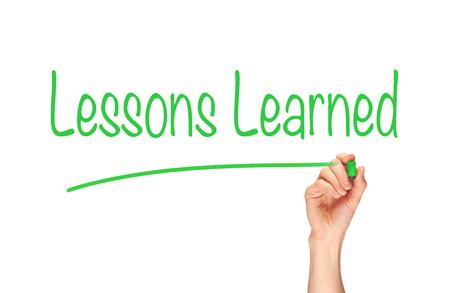 La main d'une femme écrivant le mot «Leçons apprises» sur un écran clair. Banque d'images