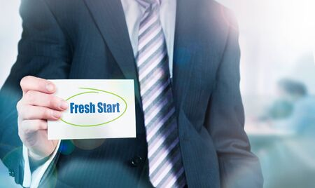 Businessman holding a card with Fresh Start written on it. photo