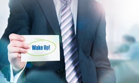 distinctness: Businessman holding a card with Wake Up! written on it.