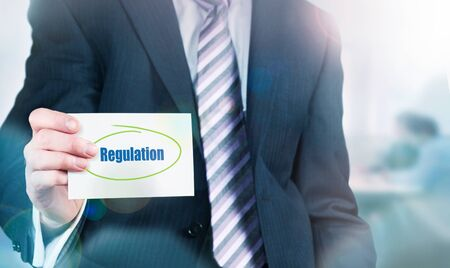 governing: Businessman holding a card with Regulation written on it. Stock Photo