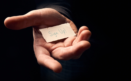 joining forces: A man holding a card with a hand written message on it, Sign Up.