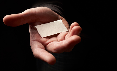 reached: A man holding a blank message card in an out reached hand.