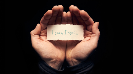 skillset: A man holding a card in cupped hands with a hand written message on it, Learn French.