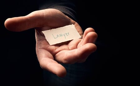 govern: A man holding a card with a hand written message on it, Lawyer. Stock Photo