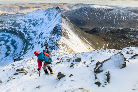 striding: A hiker descending Helvellyn towards Striding Edge and Red Tarn in the Lake District, UK.
