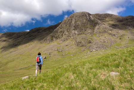 the crag: A hiker heads towards Grey Knotts and Gillercombe Crag. Lake District UK.
