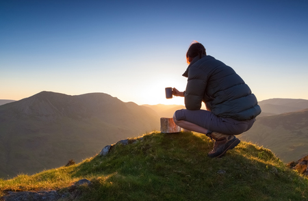 lake district england: A hiker enjoying a hot drink at sunset on Fleetwith Pike. Lake District UK. Stock Photo