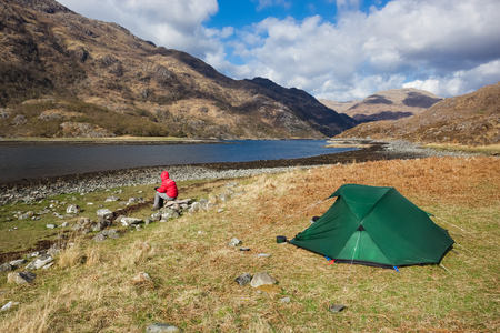 wilding: A hiker wilding camping at Barrisdale Bay beside Loch Hourn in the Scottish Highlands.