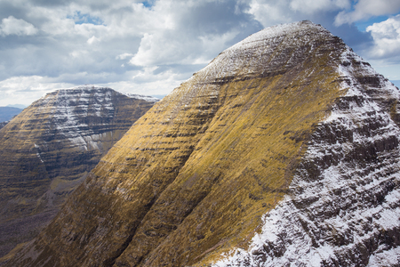 mount tom: Ben Alligin. The large wedge shape summit of Sgurr Mhor with snow on the sheltered side with Tom na Gruagaich on the left. Stock Photo