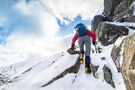 Climber ascending a snow covered ridge in the Lake District UK. Swirral Edge on Helvellyn.