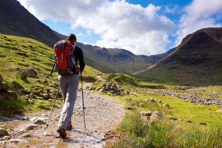 cumbria: A walker approaches Seathwaite Fell in the Lake District, Cumbria, UK on a bright spring day.