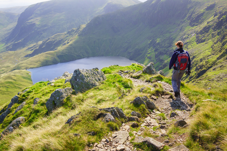 crag: A female hiker walking down Long Stile towards Rough Crag with Blea Water in the distance in the Lake District.