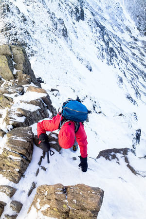 striding: Climber ascending a snow covered Striding Edge ridge below Helvellyn in the Lake District UK.