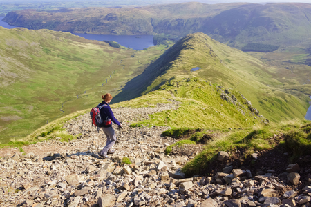 the crag: A female hiker walking down Long Stile towards Rough Crag and Haweswater in the Lake District. Stock Photo