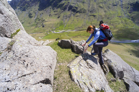 scrambling: A female climber scrambling up Cam Ridge in Langstrath valley leading to the summit of Glaramara in the Lake District.