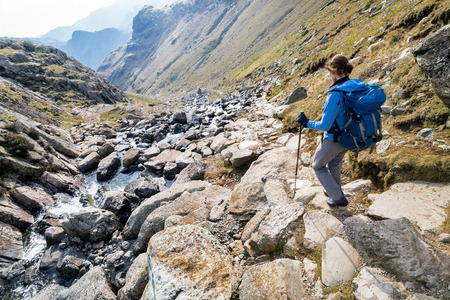 langdale: A female hiker descending Stickle Ghyll, Great Langdale in the English Lake District.