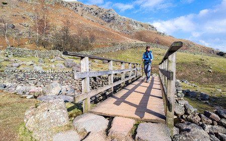 langdale: Hiker Walking across a wooden bridge at Stickle Ghyll