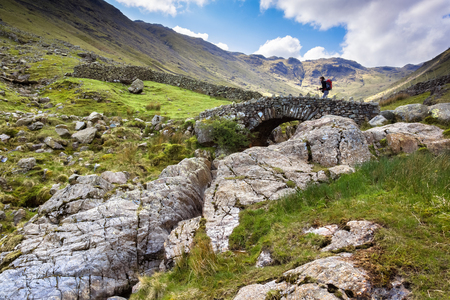 cumbria: A hiker crosses Stockley Bridge from Seathwaite Fell in the Lake District, Cumbria UK. Looking up from the stream bed. Stock Photo