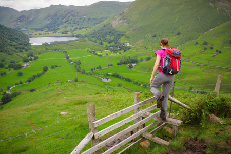 stile: A hiker crossing a stile at High Hartsop Dodd with Brothers Water in the distance. Lake District.