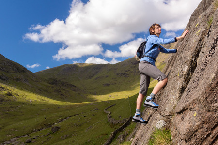 scrambler: Female rock scrambler climbing up Seathwaite Slabs, Lake District, UK.