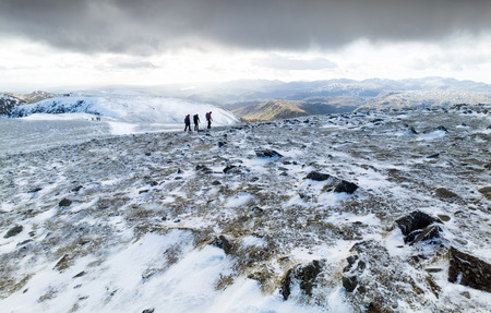 summit lake: Three hikers crossing the summit of Helvellyn in winter, Lake District UK.